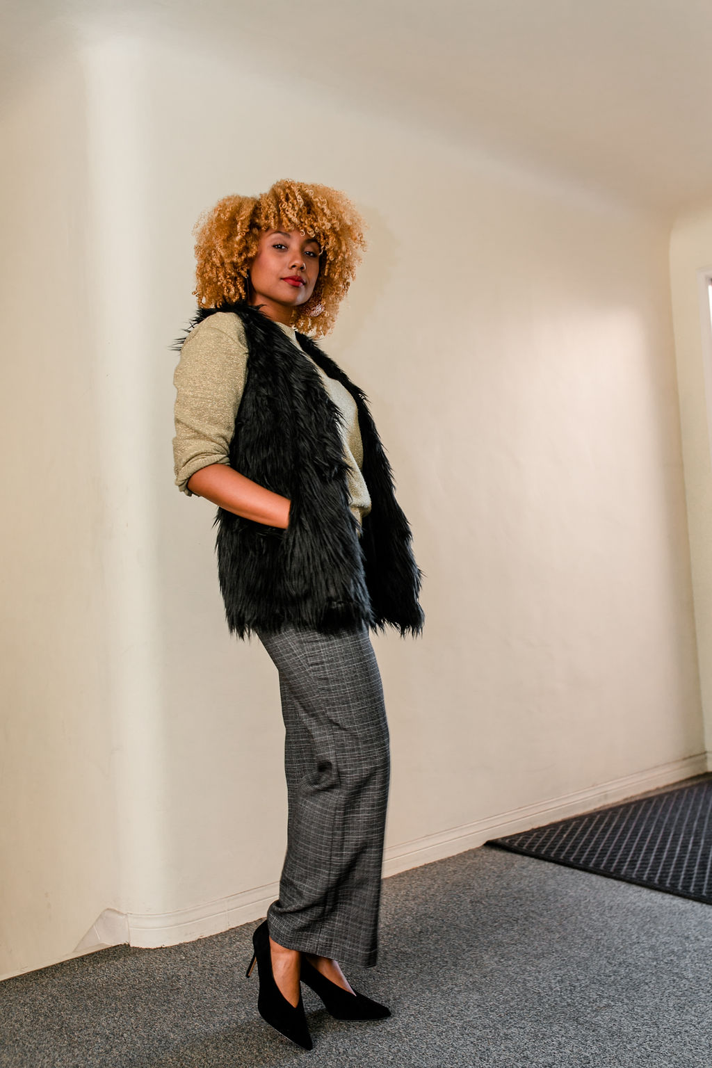 Black girl with curly blonde hair wearing slacks, fur vest and gold sweater- reflect